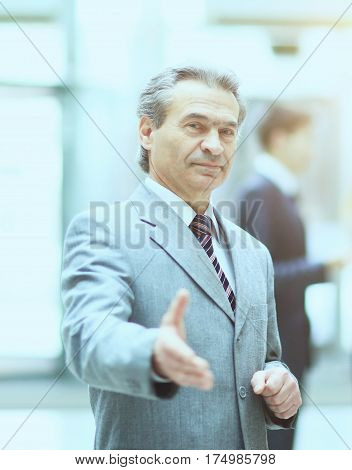 Welcoming business man ready to handshake with hand extended