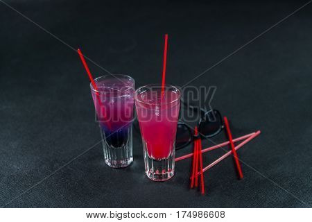 Two colored drinks a combination of dark blue with purple the second combination of red with pink long drink glass black sunglasses party set