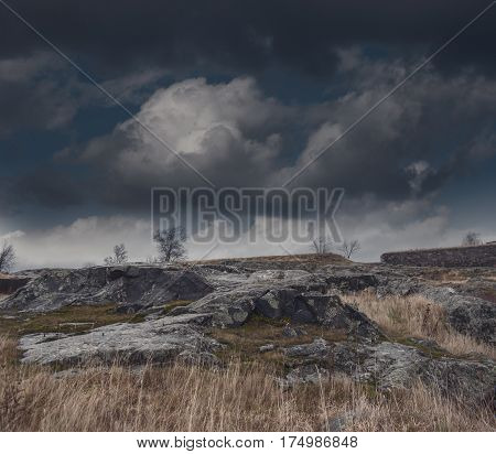 Dark gloomy foggy landscape with rock and clouds