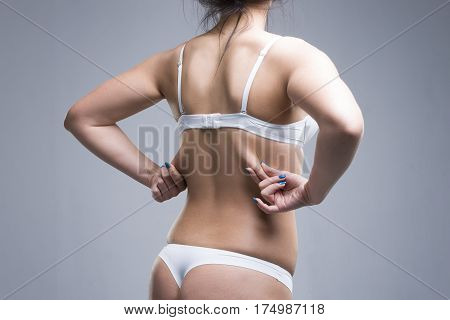 Woman holding fold of skin cellulite on female body gray background studio shot