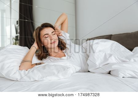 Smiling young woman with closed eyes lying and stretching in bed at home