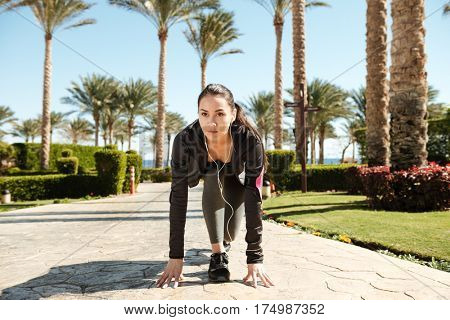 Concentrated young sportswoman with armband and earphones ready to run on summer resort