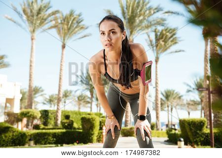 Fitness woman with armband standing and listening to music from blank screen mobile phone in summer