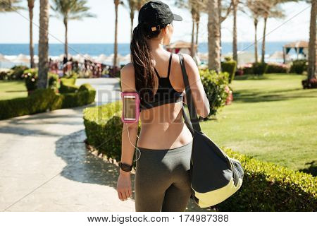 Back view of sportswoman with blank screen cell phone in armband holding bag and walking on summer resort