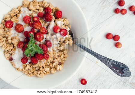 Healthy breakfast - granola with fresh milk yoghurt and wild strawberries served in a bowl with honey on white wooden table. Summer food concept. Top view.