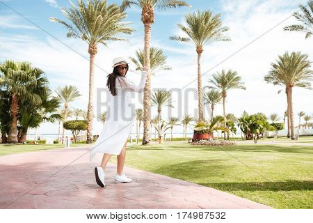 Happy cute young woman in hat and sunglasses walking and dancing on summer resort