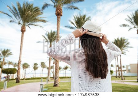 Back view of woman with long dark hair and hat walking on summer resort