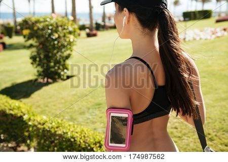 Closeup of woman athlete in cap with blank screen smarrtphone in armband in summer