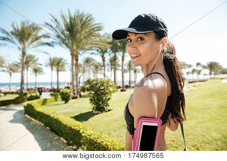 Happy young fitness woman in cap listening to music from blank screen smarphone on summer resort