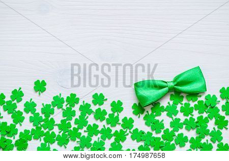 St Patrick's Day background. St Patricks Day - green quatrefoils and bow tie on the white wooden background. St Patrick's Day background with St Patrick's Day symbols. St Patrick's Day concept.