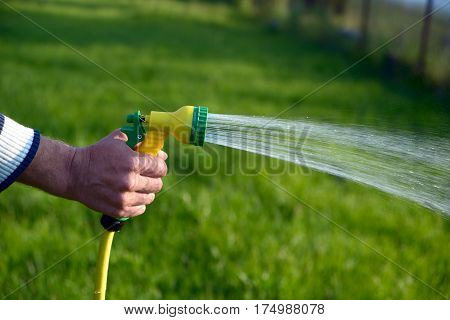Hand holding a hose for watering with the sprayed stream