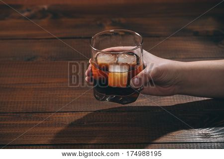 The Woman Holds In Her Hand Cola With Cognac Or Rom In Glass And Ice Cubes On Wooden Background. Fre