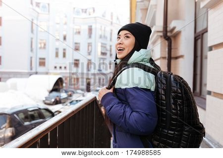 Side view of Smiling Asian woman in warm clothes and with backpack which standing on the street and looking up