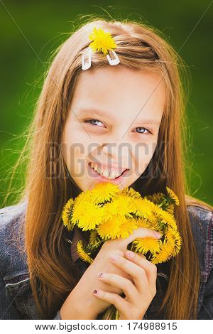 Portrait of spring girl. Closeup of beautiful young smiling girl with bouquet of yellow dandelions in hands isolated on green grass background. Age of kid is 11 years old.