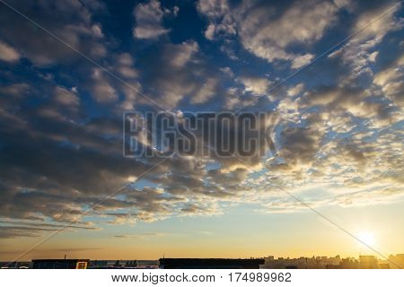 Sunset cityscape background with spindrift clouds and dramatic sky