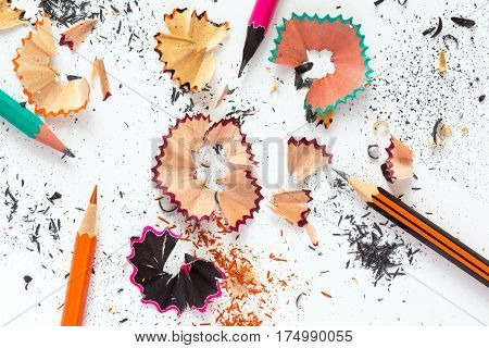 Creativity Concept Image of color Pencils and shaped wood Chips and Shavings of sharpening a pencil on white Table