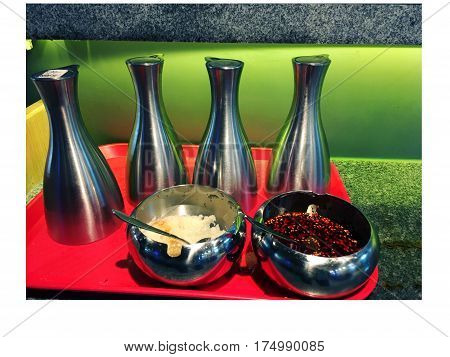 Photo of different sauces and condiments on a table in a cafe food dips and sauces in bottles and two sauces Bowls with chilli red pepper garlic paste