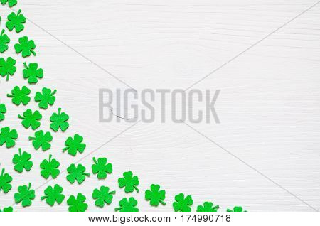 St Patrick's Day concept. St Patrick's Day background - border of green quatrefoils on the white wooden surface. St Patrick's Day background with St Patrick's Day symbols. St Patrick's Day background