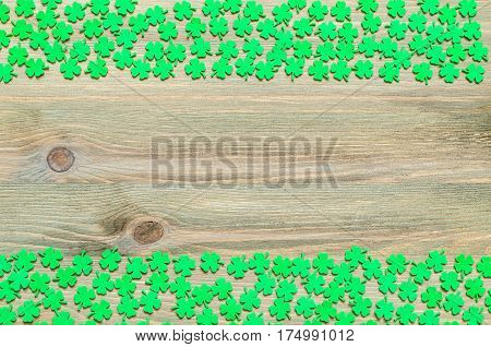 St Patrick's Day concept. St Patrick's Day background - borders of green quatrefoils on the natural wooden surface. St Patrick's Day background with clover borders. St Patrick's Day concept, free space for text. St Patrick's Day background