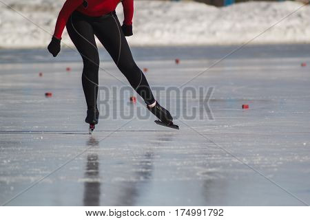 Woman's legs on skates ice rink - winter sport at sunny day, telephoto close up