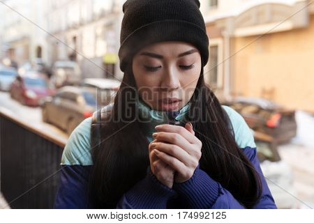 Frozen Asian woman in warm clothes which standing on the street and trying to keep warm