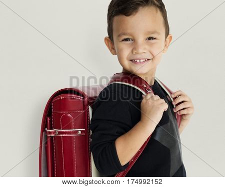 Young asian kid student with a backpack studio portrait