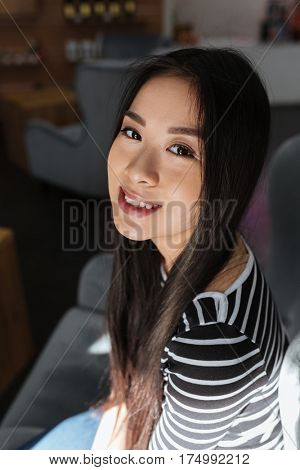 Vertical image of Asian woman in sweater which sitting on chair in cafeteria and looking at camera. Side view. Close up portrait