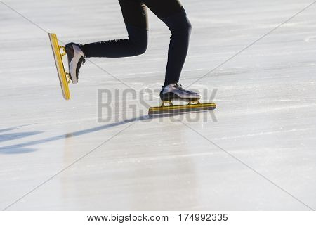 Golden skates at ice rink - winter sport concept, telephoto close up
