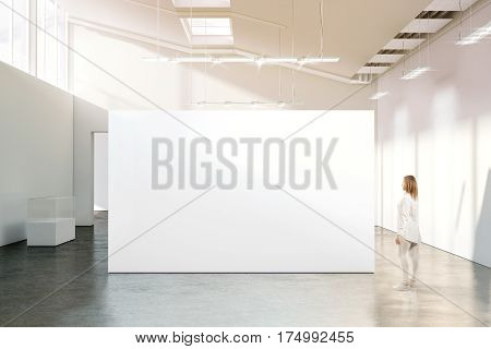 Woman walking near blank white wall mockup in modern gallery. Girl admires a clear big stand mock up in museum with contemporary art exhibitions. Large hall interior banner exposition show