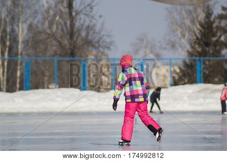 Little adorable girl on ice-rink - skating sport, telephoto
