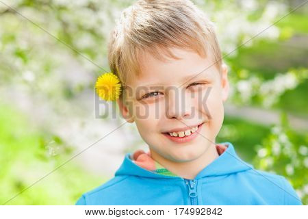 Closeup portrait of cute funny little boy isolated over green blooming trees background. Caucasian blonde child enjoying sunny warm weather in spring beautiful day.