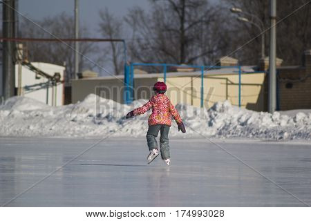 Rear view of little girl on ice-rink - children's skating sport, telephoto