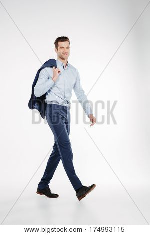 Vertical image of man in business clothes which walking in studio and looking at camera. Isolated white background