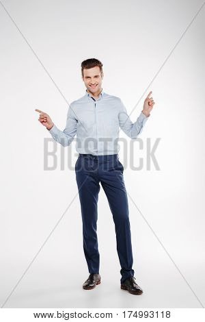 Vertical image of Man in business clothes which posing in studio and pointing up