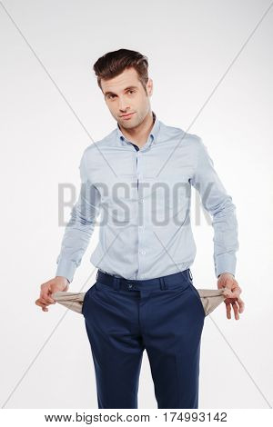 Vertical image of Upset Man in business clothes which showing empty pockets. Isolated white background
