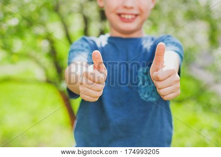 Handsome cheerful 9 years old boy showing two hands with thumbs up into camera as symbol of success. Close up of fingers with focus at them and blurry face of blond cute happy kid.