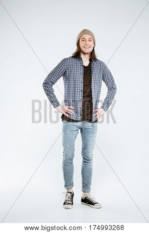 Vertical image of Smiling hipster which posing in studio with arms on hip and looking at camera. Isolated gray background
