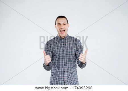 Happy man in shirt with open mouth which showing thumbs up. Isolated gray background