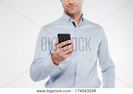 Cropped image of calm man in shirt which using smartphone in studio. Isolated white background
