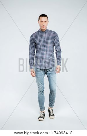 Vertical image of serious man in shirt and jeans which posing in studio. Isolated gray background