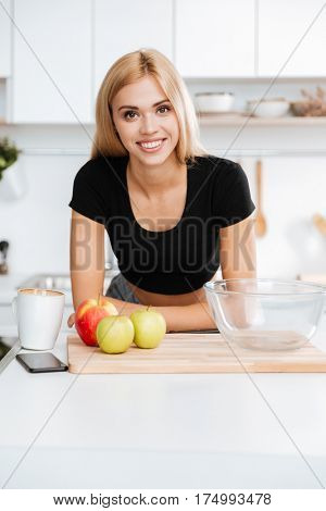 Vertical image of woman in t-shirt which standing in kitchen and looking at camera