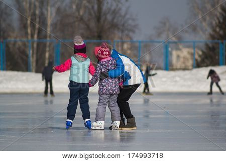 Happy family on ice-rink - children's skating sport, rear view