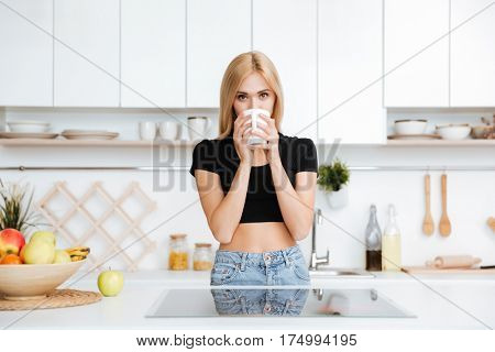Blonde Woman drinking tea in kitchen and looking at camera
