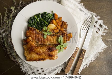 Turkey with spinach and pumpkin on a wooden table