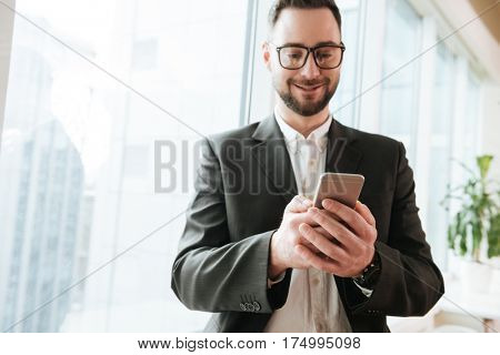 Bearded business man in suit ad eyeglasses which using smartphone near the window