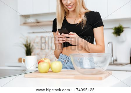 Cropped image of Smiling woman which using smartphone on kitchen