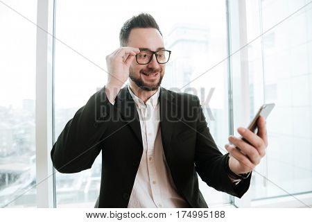 Bearded business man in suit and eyeglasses which looking at smartphone