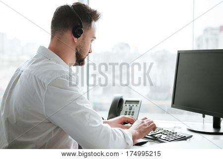 Side view of man in shirt and headset which sitting by the table and using computer