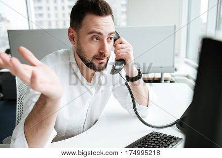 Uncomprehending man in shirt which sitting by the table and talking on phone
