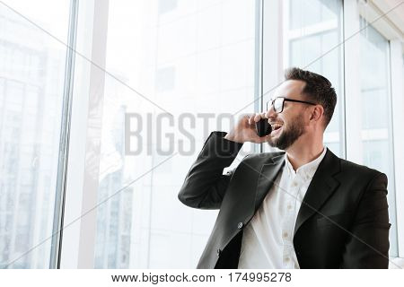 Happy Bearded business man in suit and eyeglasses which talking on phone and looking at window